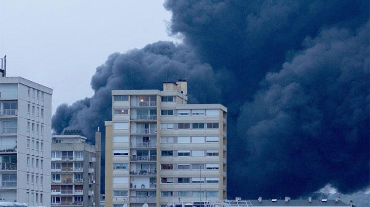 Derrière des immeubles, la fumée noire qui s'échappe de l'usine Luzibrol à Rouen, le 26 septembre 2019. (THIBAUT DROUET / AFP)
